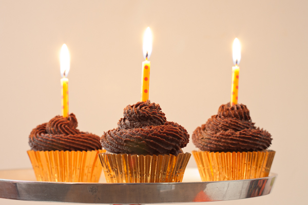 Three vanilla cupcakes with lit birthday candles set in fudgy frosting swirls.